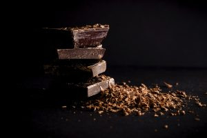 a stack of chocolate bars next to chocolate shavings