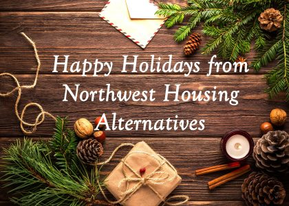 The text Happy Holidays from Northwest Housing Alternatives against the backdrop of a wooden table covered in pinecones, candles, and a package wrapped with string