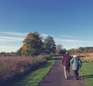 Two elderly people arm in arm walking down a path with trees in the background