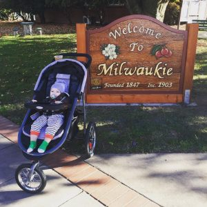 A baby in a stroller in front of a Welcome to Milwaukie sign