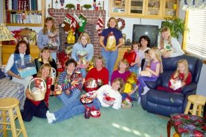 A group of women in front of a fireplace with stockings hung holding gift baskets