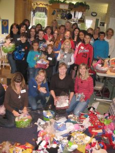 A large group of women holding gift baskets with toys and other items on the floor in front of them