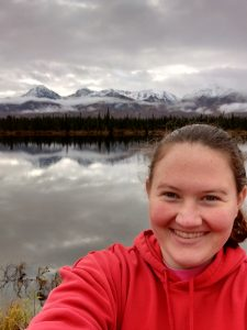 Headshot of Kelsey Allrich with mountains and a lake in the background