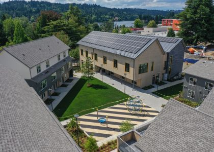 Aerial photo of the Northwest Housing Alternatives campus featuring the solar panels on the NHA offices with the Willamette River in the background.
