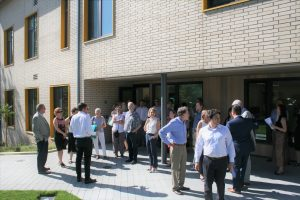 A crowd of people gathered around the front entrance of the NHA office on a bright sunny day.