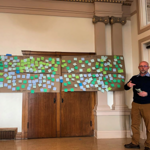 Trell Anderson standing in front of two timelines covered in post-it notes taped against the wall behind him