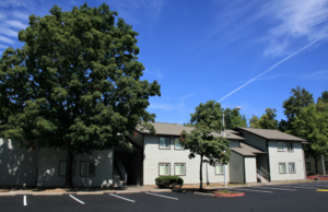 Photo of a two-story affordable housing complex called River Glen on a bright sunny day with a blue sky and large tree.
