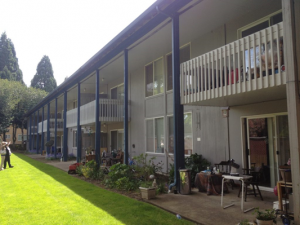 photo of College Manor, a two-story building with patios on the first floor and balconies on the second floor.
