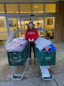 Sonia with two shopping carts full of donated fabric