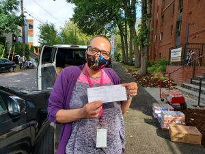 Beezie, a resident services coordinator, holds a check for the PDX Diaper Bank.