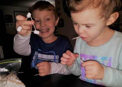 Two kids connecting marshmallows with toothpicks as part of a STEM education initiative.